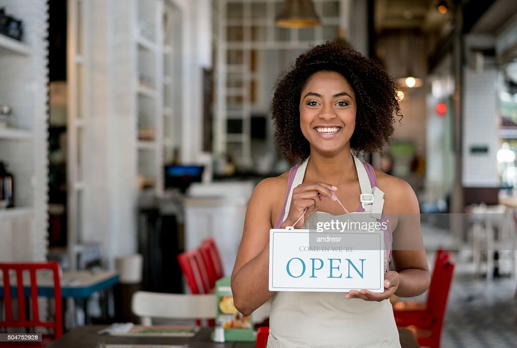 Waitress holding an open sign at a restaurant : Stock Photo
