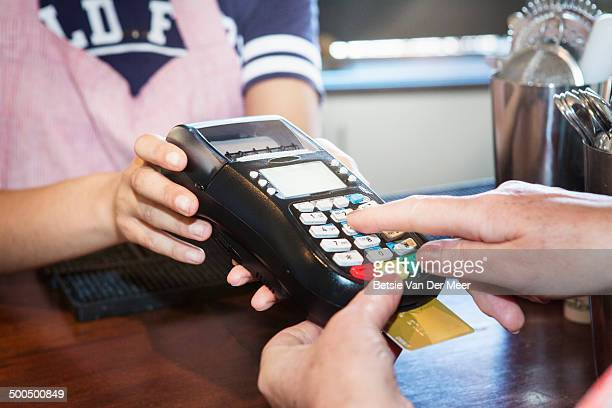 waitress holding card reader, woman paying.