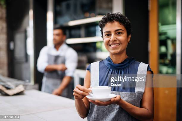 Waitress holding cup of coffee in bar