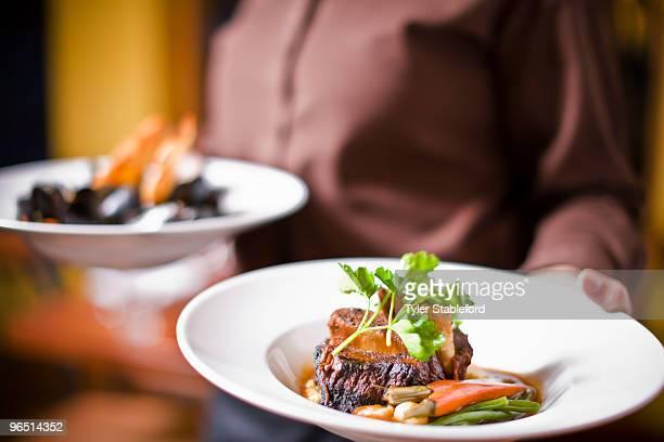 Waitress holding plate of beef tenderloin