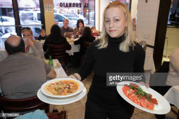 Waitress holding plates of food at Il Fornaio restaurant on Mulberry Street.