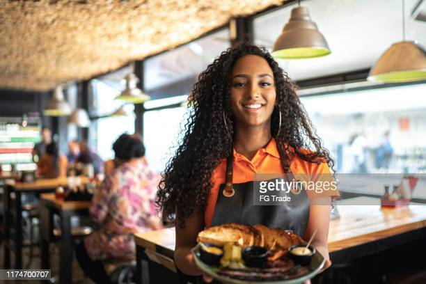 waitress holding / showing a sandwich - waitress stock pictures, royalty-free photos & images