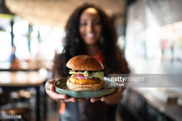 waitress holding / showing a sandwich - hamburger stock pictures, royalty-free photos & images