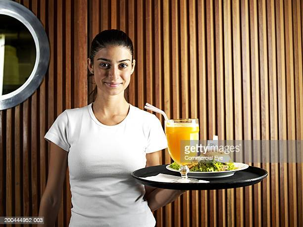 Waitress holding tray with burger and juice, portrait