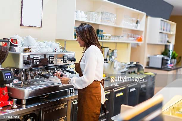 Waitress in a coffee bar making fresh coffee