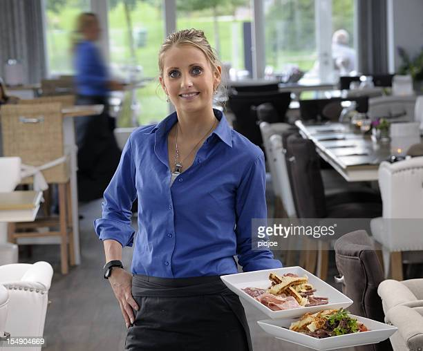 waitress in restaurant holding two plates with food - baloney stock photos and pictures