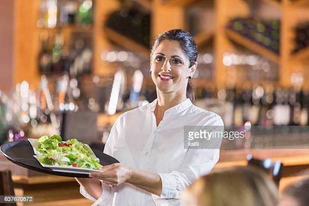 Waitress in restaurant serving food to customers