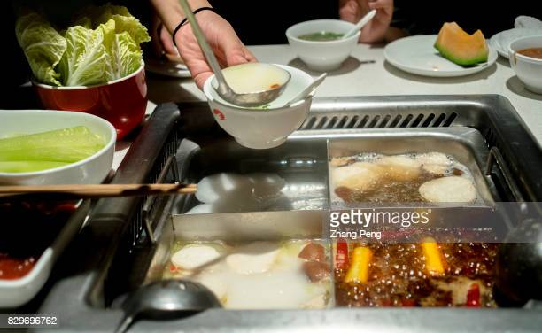 A waitress is ladling a bowl of soup for the customers Haidilao is China's most famous hotpot catering brand known its delicate service and used as...