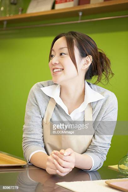 Waitress leaning on bar, smiling, looking away