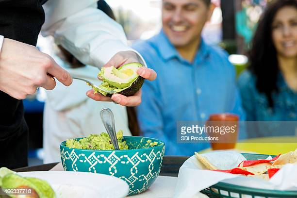Waitress making table side guacamole for customers in restaurant
