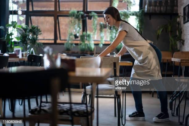 cameriera che organizza i tavoli in un ristorante - sistemazione foto e immagini stock