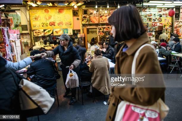 A waitress passes food to a colleague at a street food stall in Ameya Yokocho market on January 4 2018 in Tokyo Japan Ameya Yokocho claimed to be...