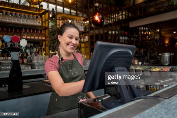 Waitress placing an order on the computer at a bar