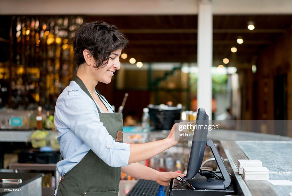 Waitress placing an order on the computer : Stock Photo