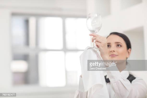 Waitress polishing wine glass in restaurant