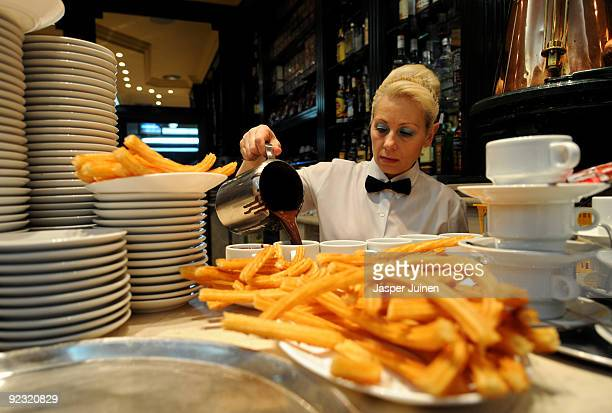 A waitress poors hot chocolat into cups to be served with Churros at the San Gines Chocolateria on October 23 2009 in Madrid Spain The ridged crunchy...