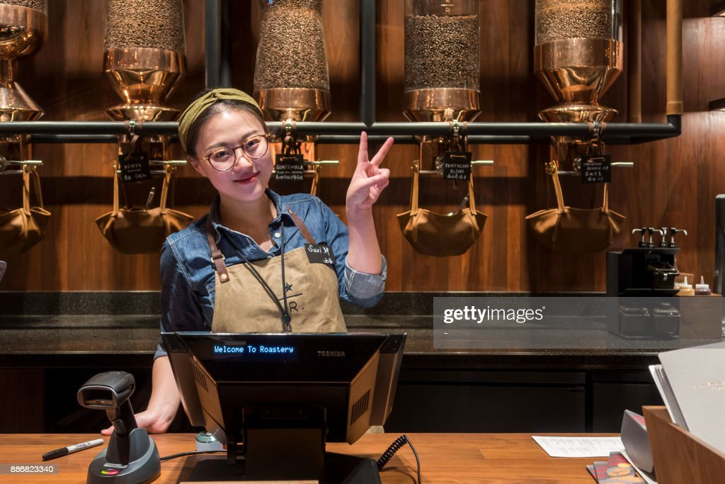 A waitress poses at the Starbucks Reserve Roastery store in Shanghai on December 6, 2017. Starbucks opened its largest cafe in the world in Shanghai on December 6 as the US-based beverage giant bets big on the burgeoning coffee culture of a country traditionally known for tea-drinking. / AFP PHOTO / - / China OUT