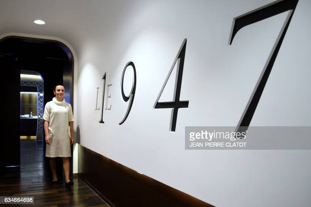 A waitress poses next to the logo of the threestar restaurant 'Le 1947' run by French chef Yannick Alleno at the fivestar palace hotel 'Le Cheval...