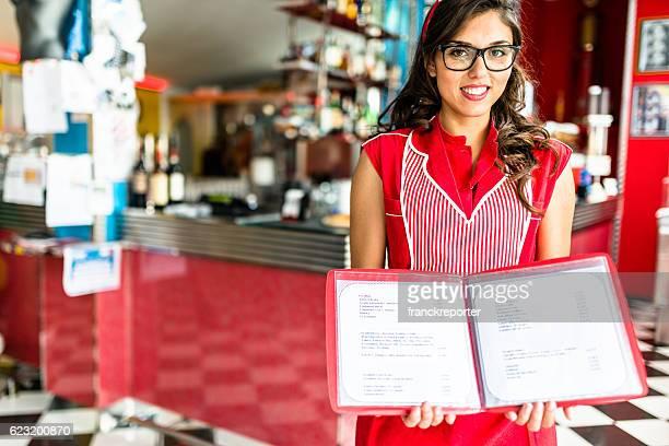 ウェイトレスのポーズを、バーカウンターでのメニューを開く