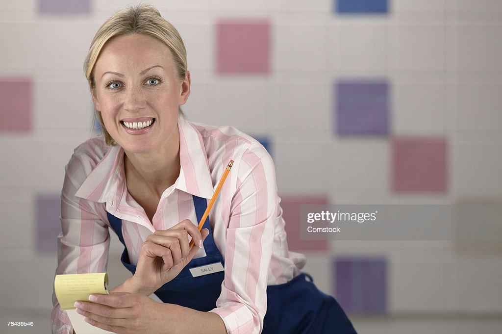 Waitress posing with notepad : Stockfoto