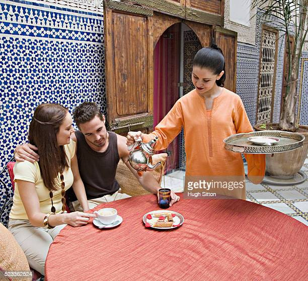 waitress pouring tea for couple - hugh sitton bildbanksfoton och bilder