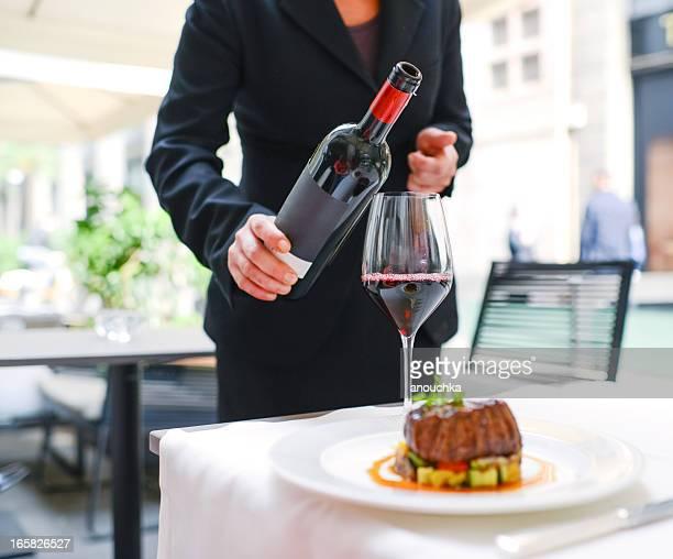 waitress  pouring wine in glass - portie stockfoto's en -beelden