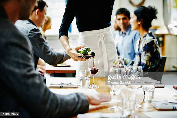 Waitress pouring wine into glass at table