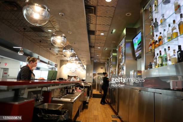 A waitress pours a beer for a customer at a restaurant at HartsfieldJackson Atlanta International Airport on April 20 2020 in Atlanta Georgia The...