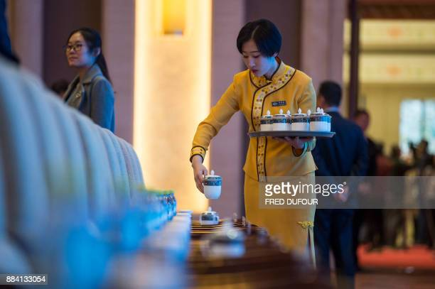 A waitress prepares cup of tea for invited visitors at the CPC in dialogue with world political parties highlevel meeting at the Diaoyutai State...