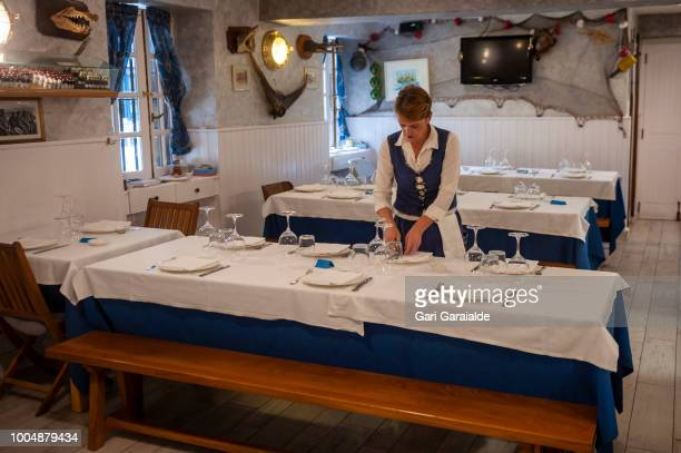 A waitress prepares the dining room at the Restaurante Hermandad de Pescadores for the lunch service on July 20 2018 in Hondarribia Spain The...