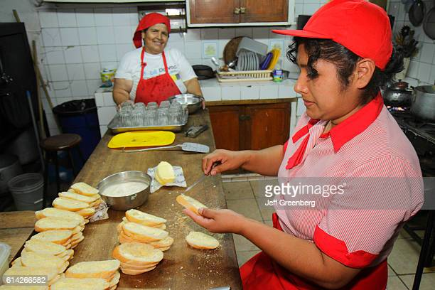 A waitress preparing food in a restaurant Avenida Miguel Grau