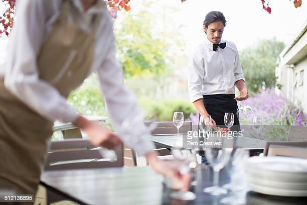 Waitress preparing wine glasses on table in patio restaurant