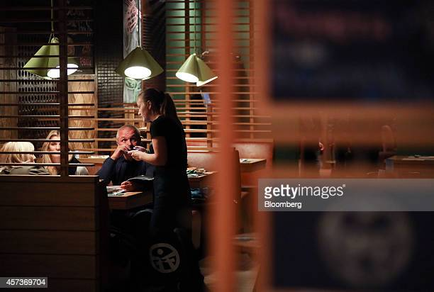 A waitress right takes customer orders in the dining area of a Planeta Sushi restaurant operated by Rosinter Restaurants Holding OJSC in Moscow...