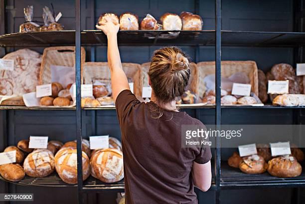 waitress selecting loaf of bread - パン屋 ストックフォトと画像