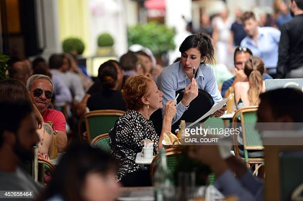 A waitress serves a customer at a restaurant in central London on July 25 2014 Britain's economy grew strongly in the second quarter overtaking the...