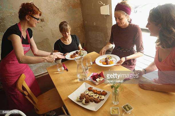 A waitress serves a dish that includes deep fried sesame balls and carrot sauce all made from discarded groceries during a media opportunity at the...