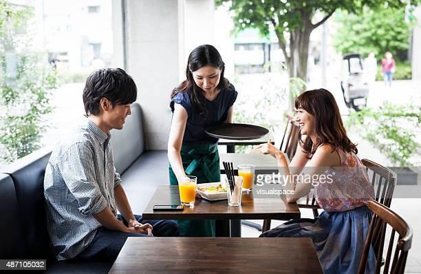 waitress serves asian couple in cafe - klanten georiënteerd stockfoto's en -beelden