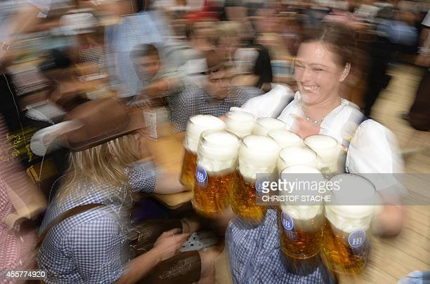 A waitress serves beer mugs during the opening of the traditional Bavarian Oktoberfest festival at the Theresienwiese in Munich southern Germany on...