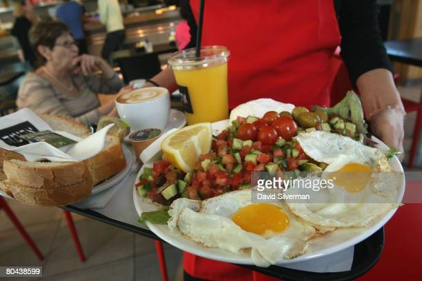A waitress serves breakfast for two including eggs cheeses salad orange juice coffee and fresh baked bread at the Aroma espresso bar on March 11 2008...