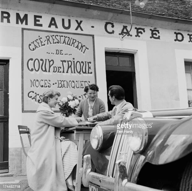 A waitress serves coffee to a couple outside the Cafe De Coup De Trique near Le Mans France July 1955 In the foreground is an MG TF sports car...