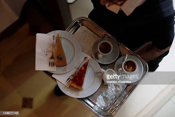 A waitress serves coffees and cakes at Cafe Demel on April 25 2012 in Vienna Austria Cafe Demel which opened its doors about 200 years ago is one of...