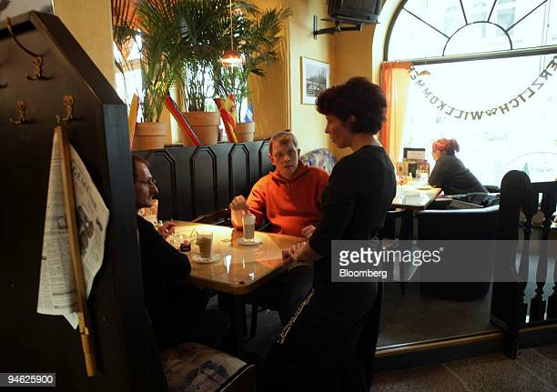 A waitress serves customers at the Altstadtcafe in Gelsenkirchen Germany Wednesday May 31 2006 Gelsenkirchen a former coal town in the Ruhr Valley of...