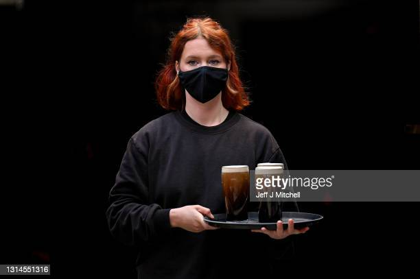 Waitress serves members of the public enjoy a drink at the Three Sisters Pub in the Cowgate as lockdown measures are eased on April 26, 2021 in...