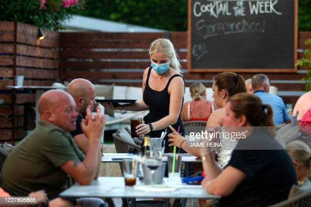 Waitress serves tourists at a restaurant in Palmanova on the Island of Mallorca on July 27, 2020. - Tour operator TUI has cancelled all British...