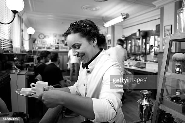 Camarera sirve un café en de barbería