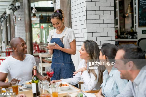Waitress serving a group of people at a restaurant