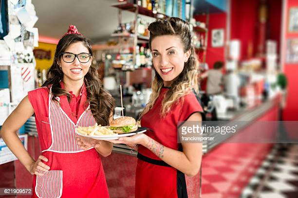 waitress serving an hamburger with french fries in a cafe
