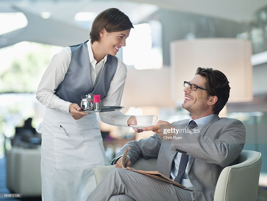 Waitress serving businessman cup of coffee in hotel lounge : Stock Photo