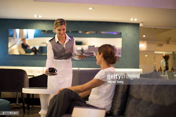 Waitress serving coffee in hotel lounge