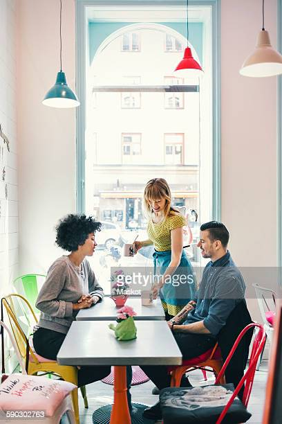Waitress serving coffee to customers in coffee shop
